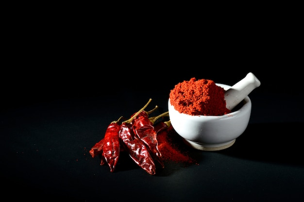 Red chili pepper powder in pestle with mortar and red chili peppers