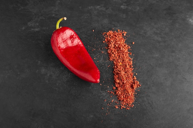 Red chili pepper with paprika on black surface.
