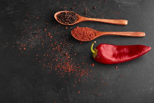 Red chili pepper with paprika in a wooden spoon.