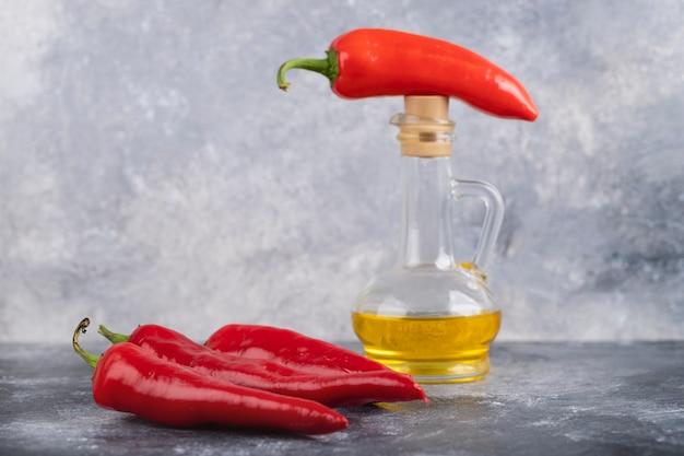 Красный перец чили и бутылка оливкового масла на мраморной поверхности.