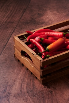 Red chili peppers in a box put on a wooden surface
