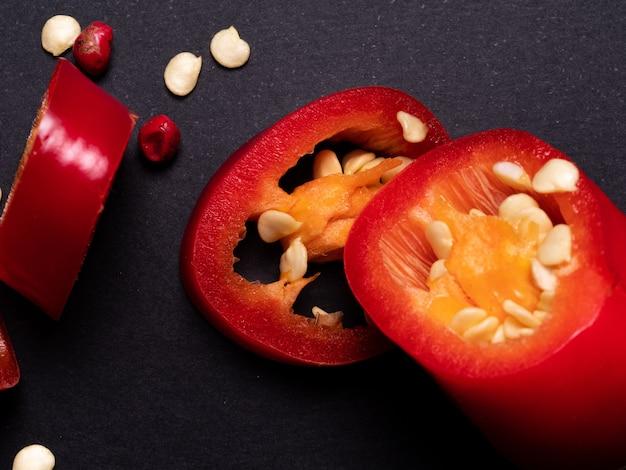 레드 칠리 페 퍼는 블랙 테이블에 조각으로 잘라. 뜨거운 향신료, 붉은 고추. 집에서 요리하십시오.