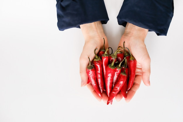 Red chili peppers in girl's hands on white background