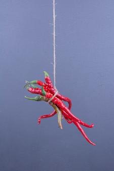Peperoncini rossi impiccati con un filo sulla superficie blu