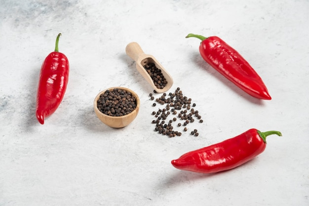 Red chili peppers and pepper grains on marble background.