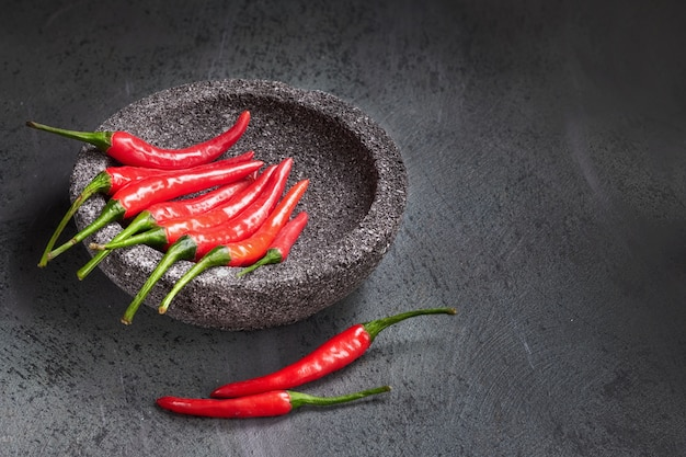 Red chili peppers in stone bowl, text space