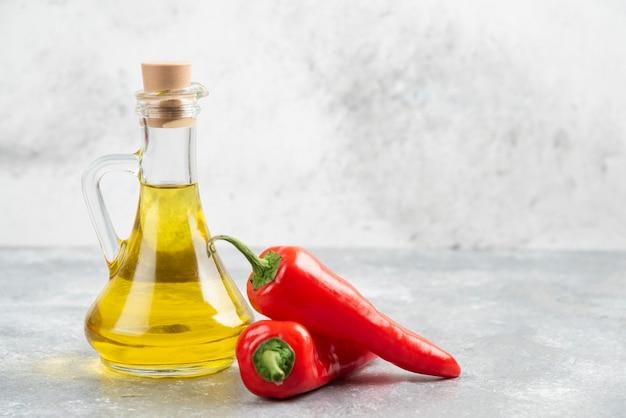 Peperoncini rossi con una bottiglia di olio extra vergine di oliva sul tavolo di marmo.
