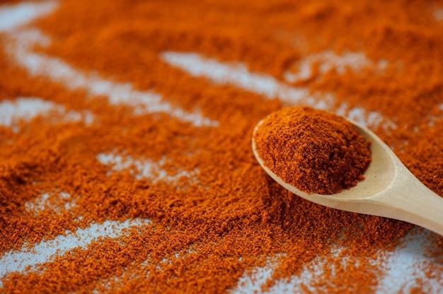 暗い背景、クローズアップの木製のボウルに赤唐辛子粉またはパプリカ。料理の材料、味。