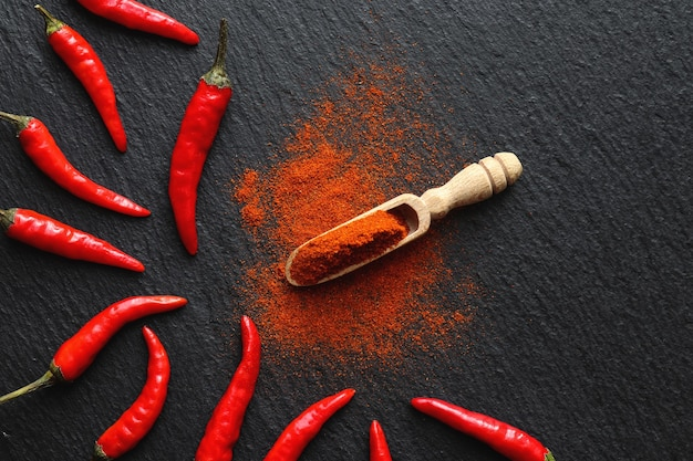 Red chili powder in wooden spoon and fresh chili peppers on the table. top view, flat lay.