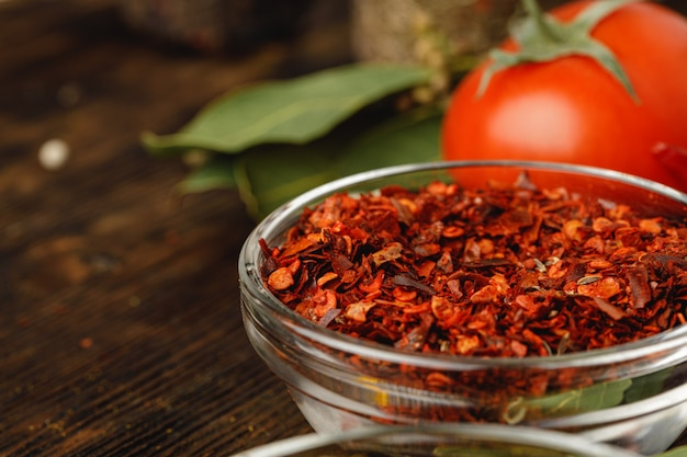 Red chili spice in glass bowl with herbs on dark table