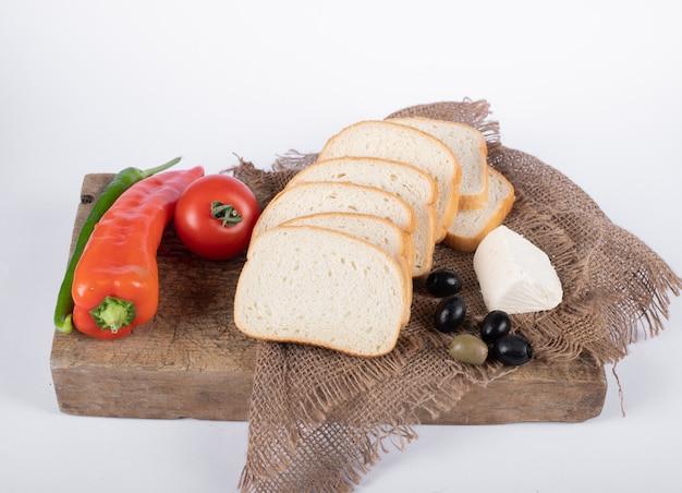 トマト、オリーブ、チーズ、木の板に白パンと赤唐辛子