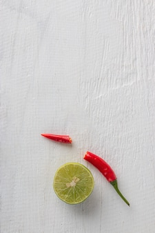 Red chilli and lemon for cooking thai food on white wooden table