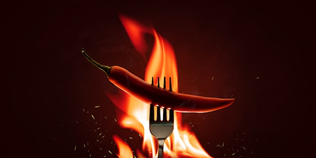 Red chilli peppers with a fork on a fire element and hot background