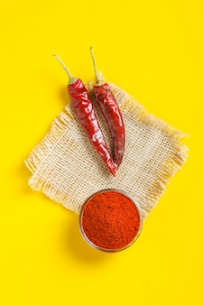 Red chilli powder in glass bowl and chilli peppers on yellow surface