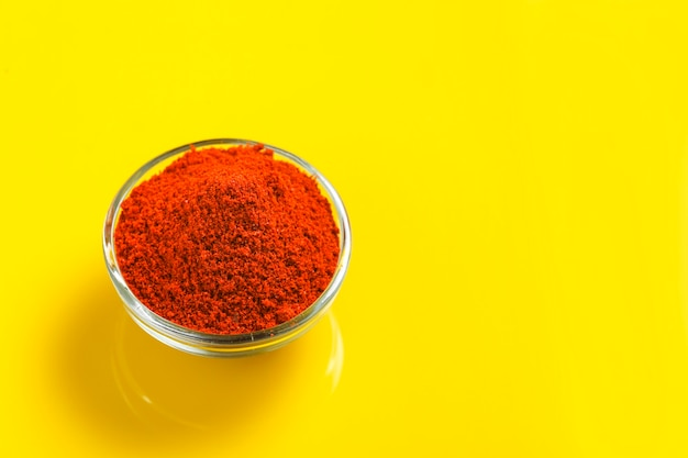 Red chilli powder in glass bowl on yellow surface top view