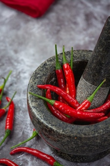 Red chillies are in a stone mortar on black surface.