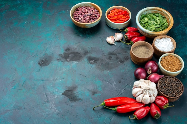 Red chilly peppers with greens onions greens garlics on dark