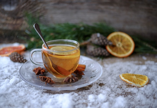 Red chinese lemon tea in glass cup on snow-covered wooden table with pine branches, cones, anise, dried oranges