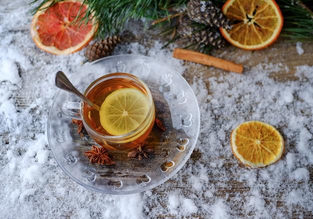 松の枝、円錐形、アニス、乾燥オレンジの雪に覆われた木製のテーブルの上のガラスカップの赤い中国のレモンティー