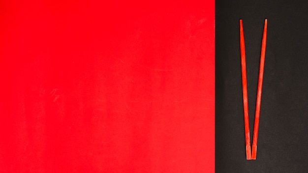 Красная палочка для еды на черной и красной двойной поверхности с местом для текста