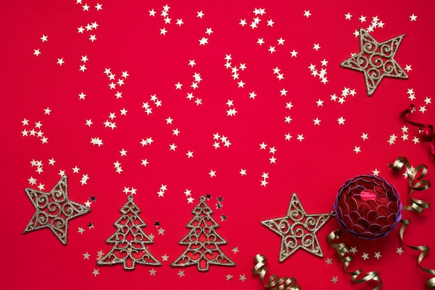Red christmas background. christmas ornaments and golden stars on bright red background.
