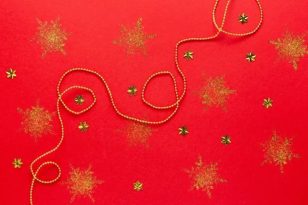 Красный новогодний фон с праздничным оформлением из золотой пластиковой гирлянды и сверкающих снежинок