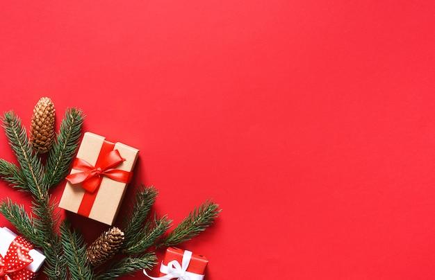 モミとリボンのギフトと赤いクリスマスの背景。新年の飾り。