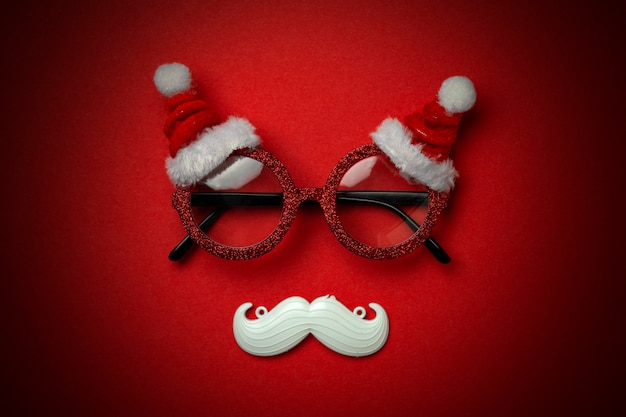 Red christmas background with santa glasses and white hipster mustache.