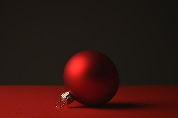 Красный елочный шар лежит на фоне темноты