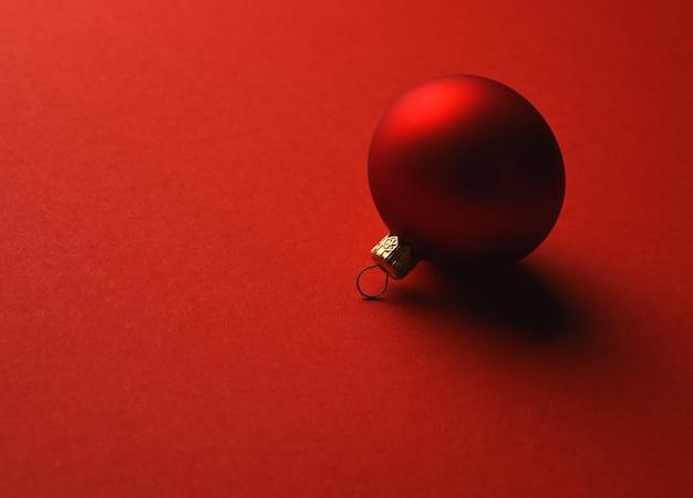 Красный елочный шар лежит на красной поверхности с тенями. фото высокого качества