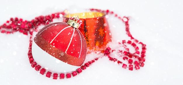 正方形のビーズとガラスの燭台で燃えているろうそくと自然な白い雪の上の赤いクリスマスボール。クリスマス、新年の屋外。降雪、おとぎ話と魔法のお祝いムード、通りの装飾。