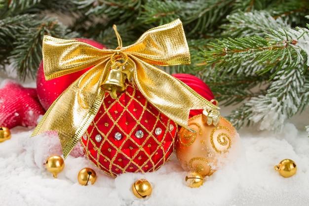 モミの木の下で雪の中で金色の弓と赤いクリスマスボール