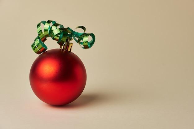 그림자가 있는 파스텔 베이지색 배경에 녹색 리본이 달린 빨간 크리스마스 공. 확대. 외딴. 축제 개념입니다.