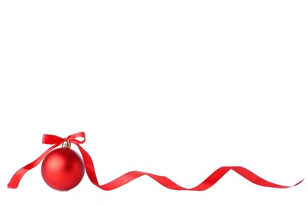 白い背景の上のリボンと赤のクリスマスボール