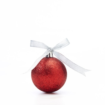 Red christmas ball with silver ribbon on white