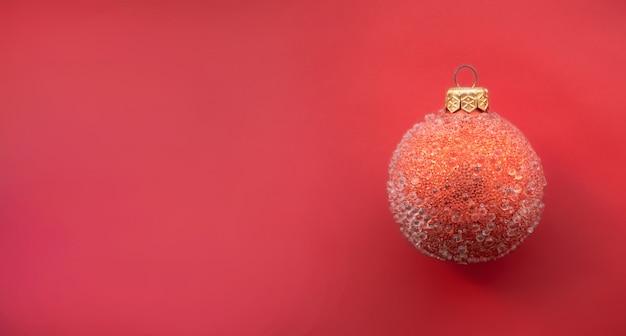 Красный елочный шар с некоторыми шишками на красном фоне минималистичный рождественский дизайн место для текста