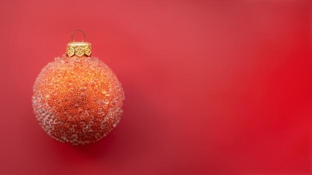 빨간색 배경에 약간의 융기가 있는 빨간 크리스마스 공. 최소한의 크리스마스 디자인, 텍스트를 위한 장소.