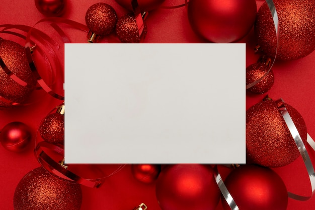 빨간색 크리스마스 볼과 빨간색 테이블에 빈 카드