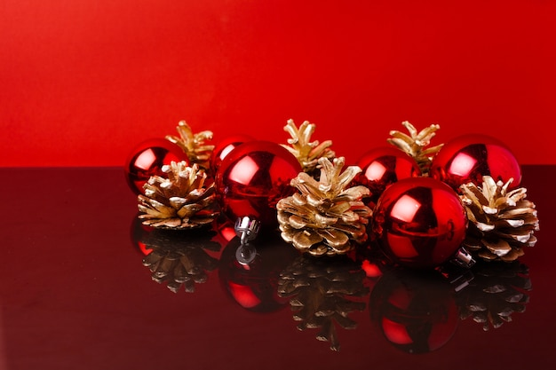 레드 크리스마스 공 및 빨간색 배경에 황금 페인트 콘