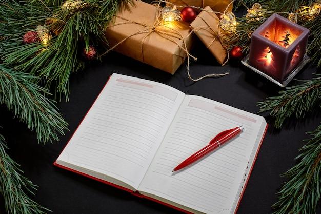 Красные рождественские шары и ноутбук, лежащие рядом с зеленой еловой веткой на черном фоне, вид сверху. скопируйте пространство. натюрморт. плоская планировка. новый год