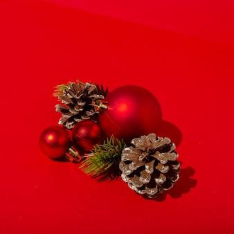 빨간색 크리스마스 볼과 빨간색 테이블에 소나무 콘