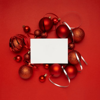 Red christmas balls and blank card on red table