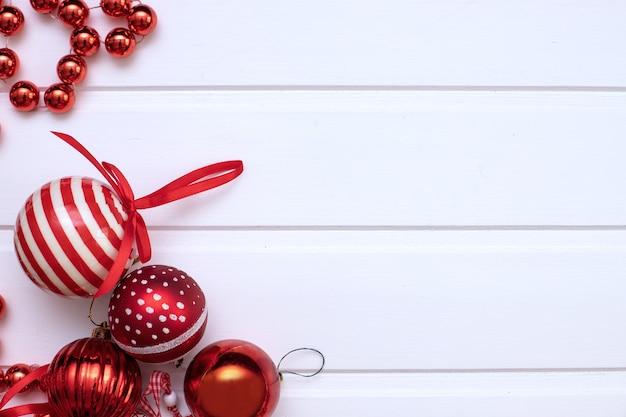 Красные елочные шары в нижнем левом углу на белом деревянном фоне