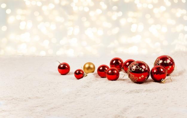赤いクリスマスボールは花輪が付いている白いニット格子縞の上にあります