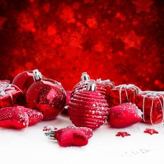 Красные елочные шары на белом снегу, красный фон боке со звездами