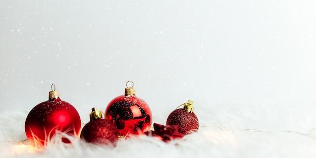 Красные елочные шары на белом с перьями.