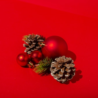 Red christmas balls and pine cones on red table