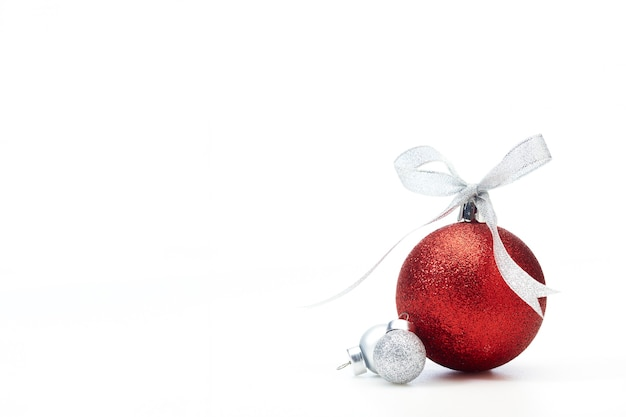 Red christmas balls with silver ribbon on white
