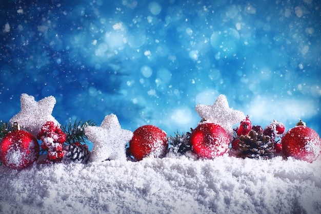 Red christmas balls with stars and garlands on snow