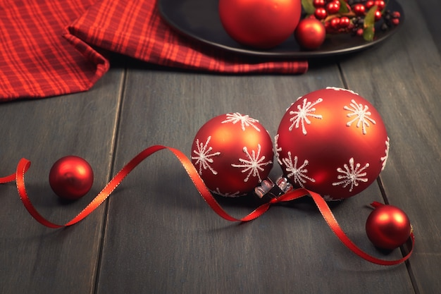 Red christmas baubles tied with ribbon and red napkin on wood